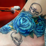 Blue rose and skull tattoo on ankle
