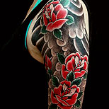 Red roses tattoo on a woman's upper arm