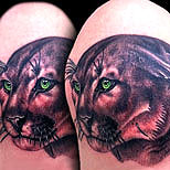 Tattoo of a big cat with green eyes
