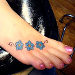 Blue flowers tattoo on foot