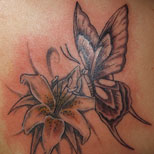 Tattoo of a butterfly on a lily