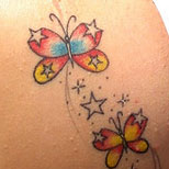 Tattoo of butterflies and stars on a girl's shoulder