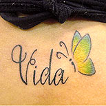 Butterfly and text tattoo on a woman's back