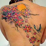 Awesome cherry blossom tattoo on a girl's back (with butterfly and sun)