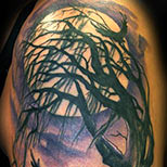 Dead tree crow tattoo on a man's arm