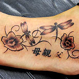 Dragonfly and kanji tattoo on a woman's foot