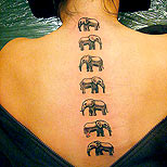 Elephant tattoos on a woman's spine