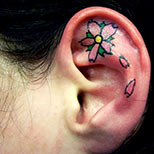 Small flower tattoo on a girl's ear