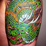 Green Japanese dragon tattoo on man's upper arm
