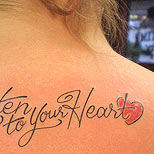 Quote tattoo on a woman's back: Listen to your heart