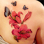 Kanji and cherry blossom tattoo on a woman's back