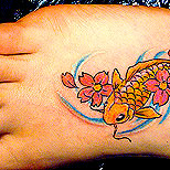 Koi fish and cherry blossom tattoo on a girl's foot