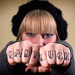 Lady Luck tattoo on a girl's fingers
