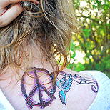 Peace sign and dove tattoo on a woman's back