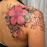 Pink flower tattoo on a woman's shoulder