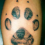tattoo of a wolf face through a paw print