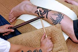 Traditional application of a tribal tattoo